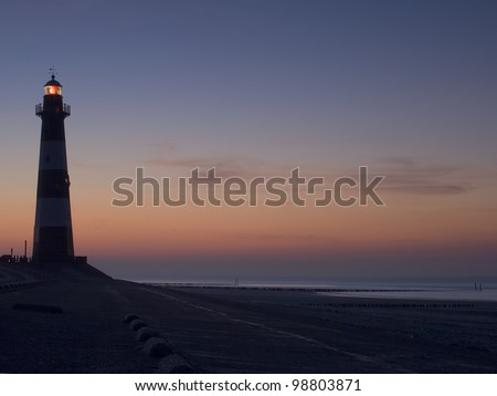 Lighthouse Breskens lighthouse in the Netherlands shining in the evening. - stock photo