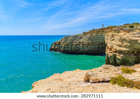 Lighthouse building on top of cliff on coast of Portugal near Carvoeiro town, Algarve region - stock photo