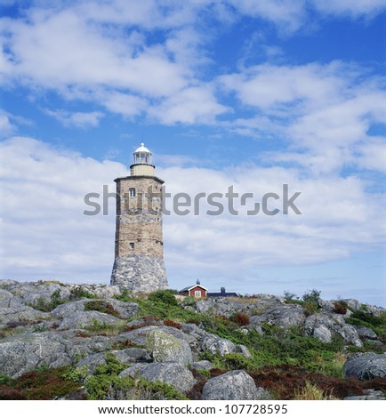 Lighthouse by rocks, low angle view