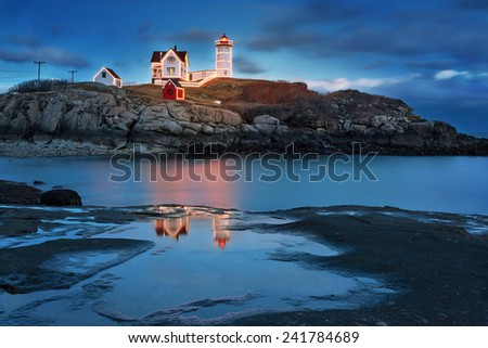 Lighthouse decorated with Christmas lights at dusk with a reflection - stock photo