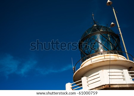 Lighthouse detail against a blue sky with some clouds. - stock photo