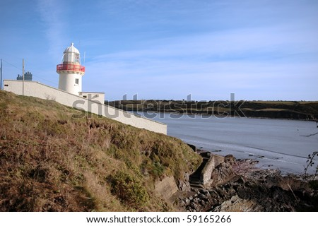 lighthouse during a sunny day on the rocks in with steps to beach in youghal county cork ireland
