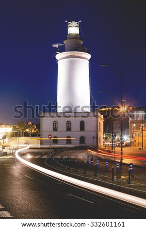 Lighthouse in Malaga, Andalusia, Spain. Night lights in the Muelle uno.