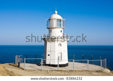 Lighthouse in sunny day near sea - stock photo