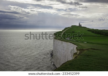 Lighthouse in the edge of famous white cliffs of Dover, England. - stock photo