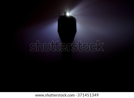 Lighthouse in the fog at night - stock photo