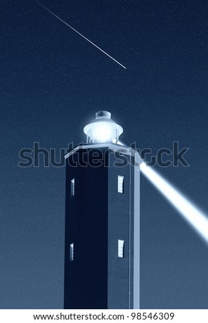 lighthouse in the night under starry sky - stock photo