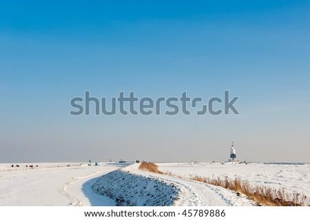 Lighthouse in winter (Marken a small village near Amsterdam) - stock photo