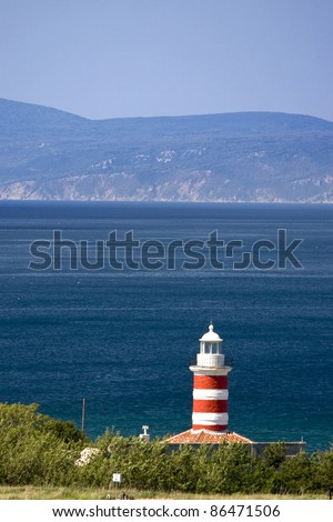 Lighthouse of the cape Ostro with the rocky coast and it`s tip - stock photo