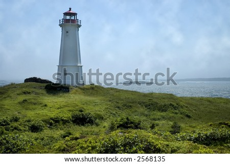 Lighthouse on a grassy hill against a cloudy summer sky
