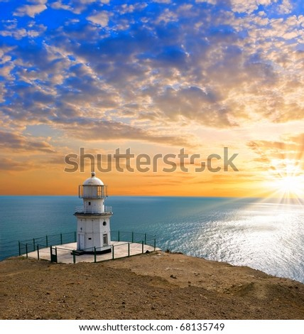 lighthouse on a marine cape at the sunset - stock photo