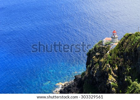 Lighthouse on a rocky coast in the Atlantic Ocean - stock photo