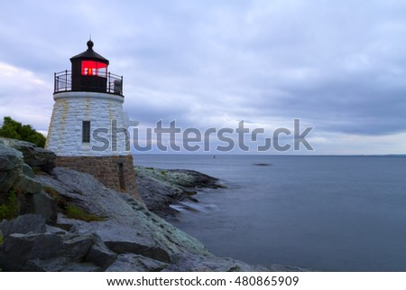 Lighthouse on a rocky shore at sunset.