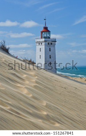 Lighthouse on a sand dune in Rubjerg Knude in Denmark - stock photo
