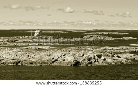 Lighthouse on a small island in the archipelago of the Aland Islands, Finland (stylized retro) - stock photo