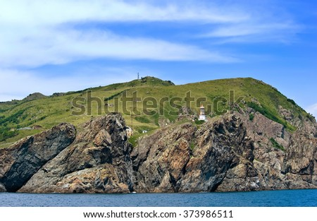 Lighthouse on a steep cliff of Cape Gamow. - stock photo