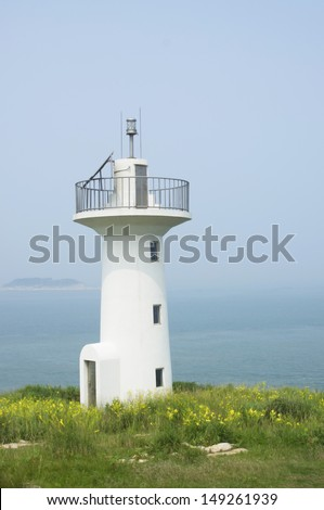 Lighthouse on an island in the sea. - stock photo