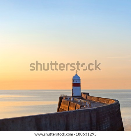 Lighthouse on breakwater wall with calm sea during sunrise.  Tranquil scene on Isle of Man - stock photo