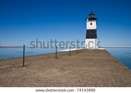 Lighthouse on Lake Erie at the end of a cement dock - stock photo