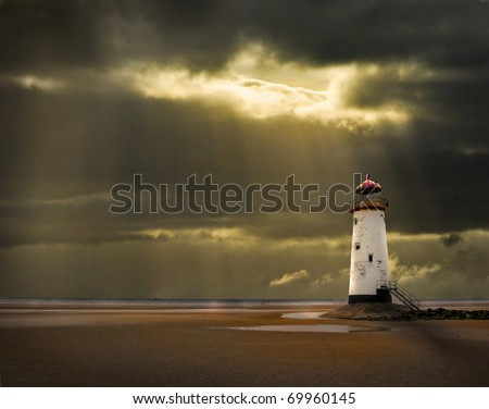 lighthouse on north wales coast illuminated in the golden afterglow of a storm at sea - stock photo