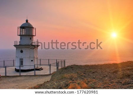 Lighthouse on the coast at dawn - stock photo