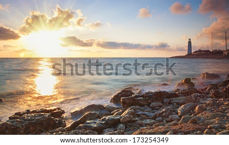 Lighthouse on the coast on the background of sky with clouds and sun - stock photo