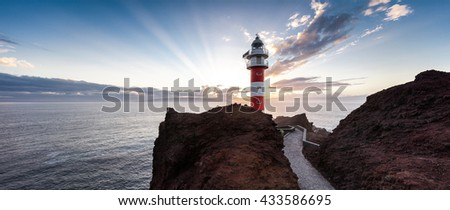 Lighthouse on the rock during sunset