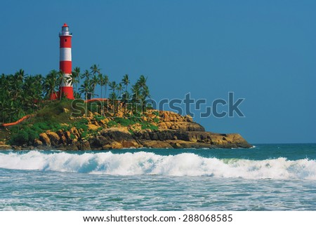 Lighthouse on the rocks near the ocean at blue sky with clouds in Kovalam, Kerala, India. - stock photo