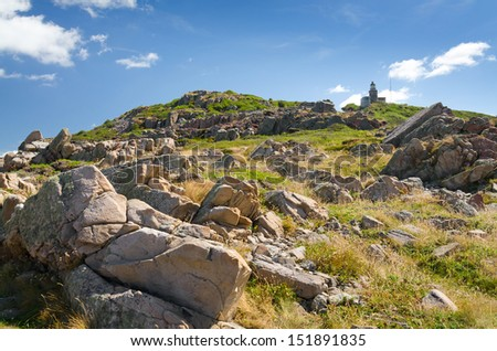 Lighthouse on the top of rocky coast - stock photo