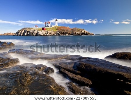 Lighthouse on top of a rocky island slow exposure - stock photo