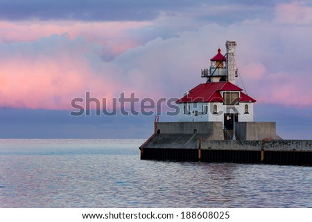 Lighthouse Overlooking Beautiful Lake Superior At Sunset with Pink and Blue Clouds - stock photo