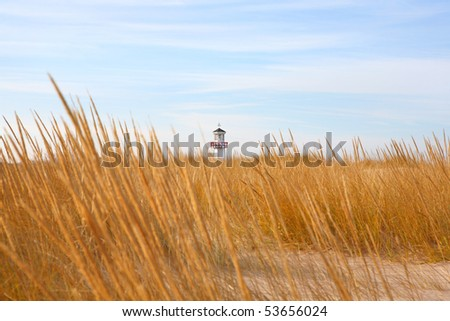 Lighthouse seen through the dunes - stock photo