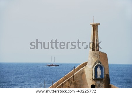 Lighthouse showing the Statue of Our Lady in a blue alcove with sailing boat in the background, Malta - stock photo