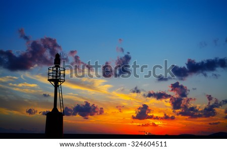 lighthouse silhouette at sunset in Alghero harbor