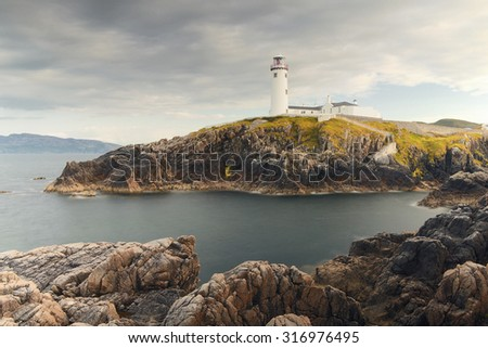 Lighthouse sitting on the edge of cliffs with blue sky in the background - stock photo
