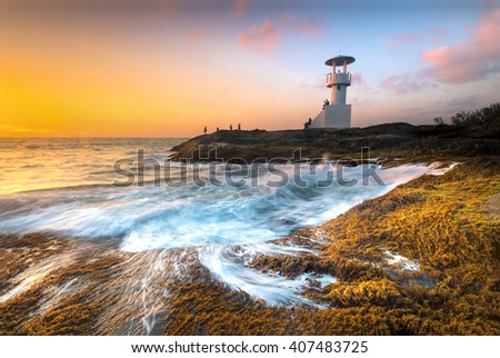 Lighthouse through the air to the sea at night. - stock photo