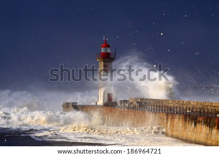 Lighthouse under heavy storm seeing waves foam in the air carried by the strong wind - stock photo