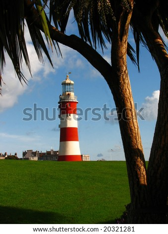 Lighthouse under palm  tree, Plymouth, UK - stock photo