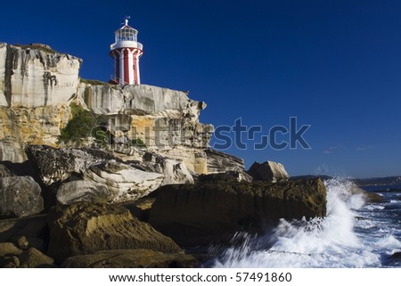 Lighthouse vertical striped navigation building on top of sandstone cliff sunny summer day pacific coast of stormy ocean with blue sky