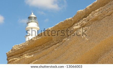 Lighthouse with a blue sky behind a textured rock. - stock photo