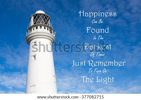 Lighthouse with a Inspirational motivational quote.of Happiness Can Be Found In The Darkest Of Times, Just Remember To Turn On The Light against a partly cloudy sky background - stock photo