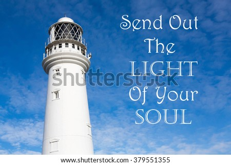 Lighthouse with a Inspirational motivational quote of Send Out The Light Of Your Soul against a partly cloudy sky background - stock photo