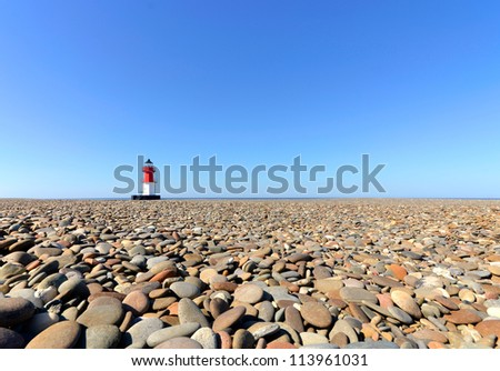 Lighthouse with Beach Pebbles in foreground. Location - Point of Ayre on the Isle of Man - stock photo