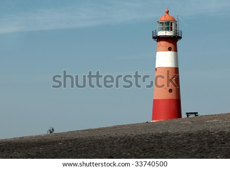 Lighthouse with bicycle and bench on a dike at the coast of the northern sea, the Netherlands, near town of Westkapelle - stock photo