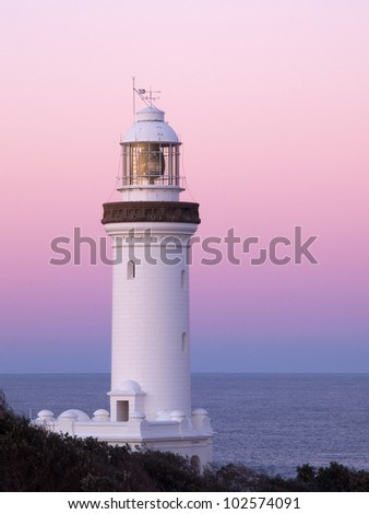 Lighthouse with sunset pink sky - stock photo