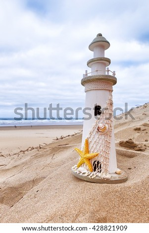 Lighthouse wooden replica on the beach with ocean in the background. Concept for summer, vacation, getaway, nautical theme. Copy space - stock photo