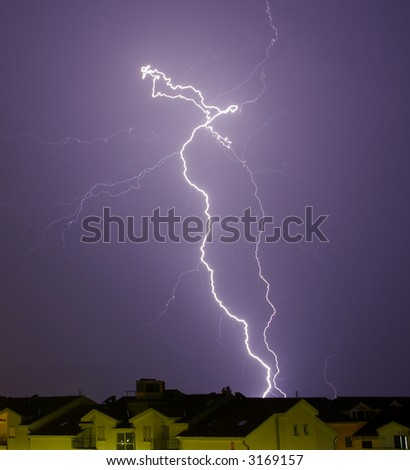 Lighting bolt over houses roofs - stock photo