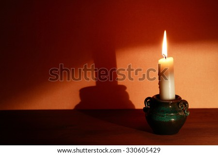 Lighting candle in candlestick with big shadow on the wall - stock photo