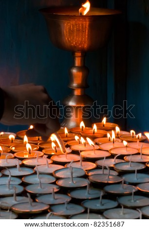 Lighting candles at a Buddhist temple - stock photo