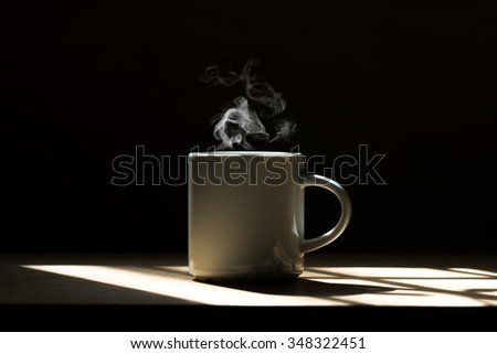 Lighting from window with hot white coffee cup on the wooden.